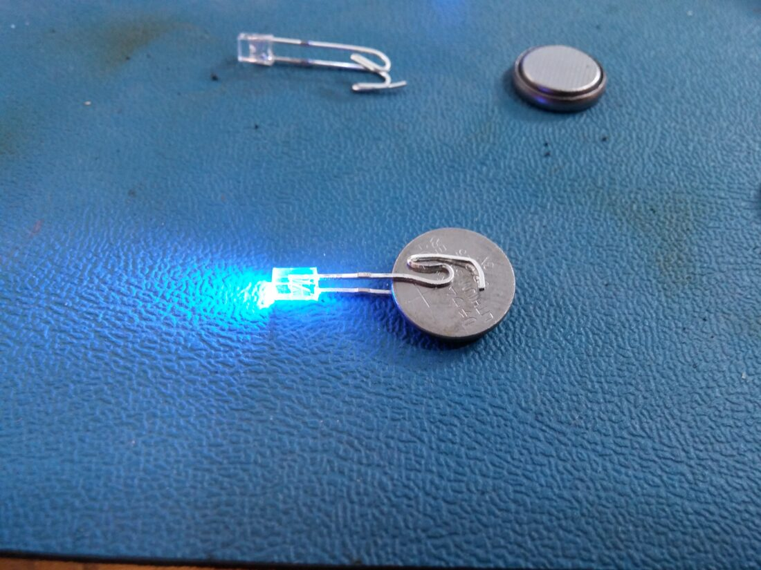 Place LED on battery. I bend leads so there is more area of electrical contact.