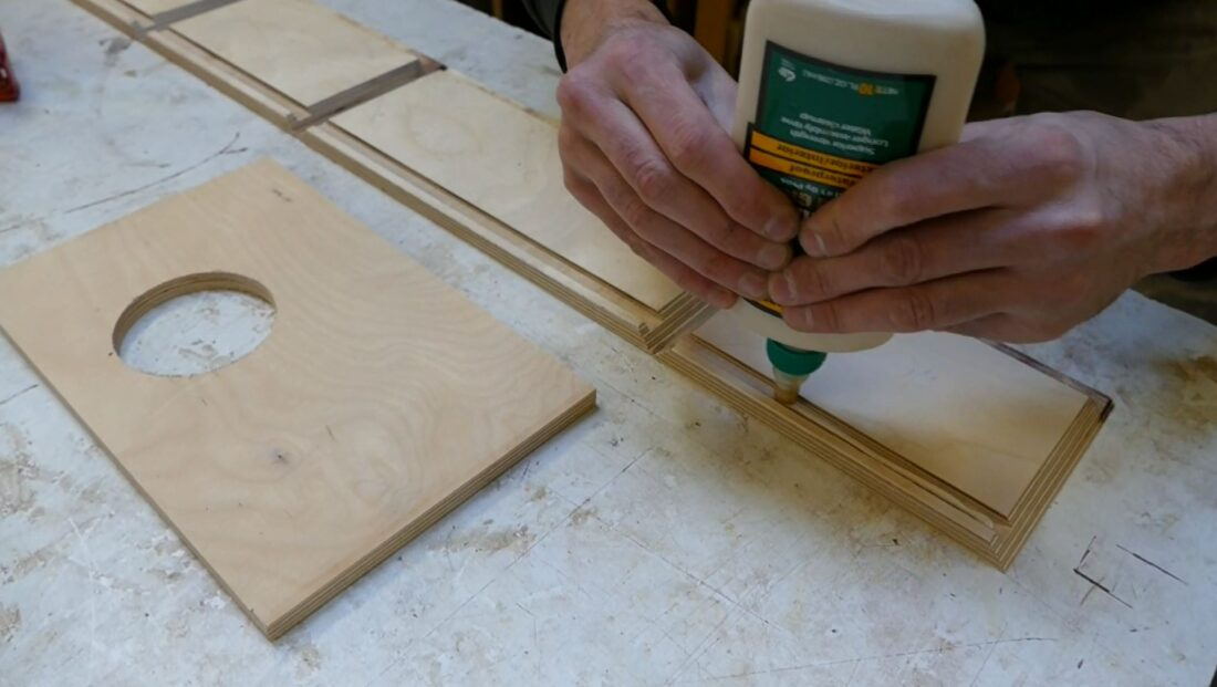 Raho spreads glue into the pre-cut grooves of the wooden housing.
