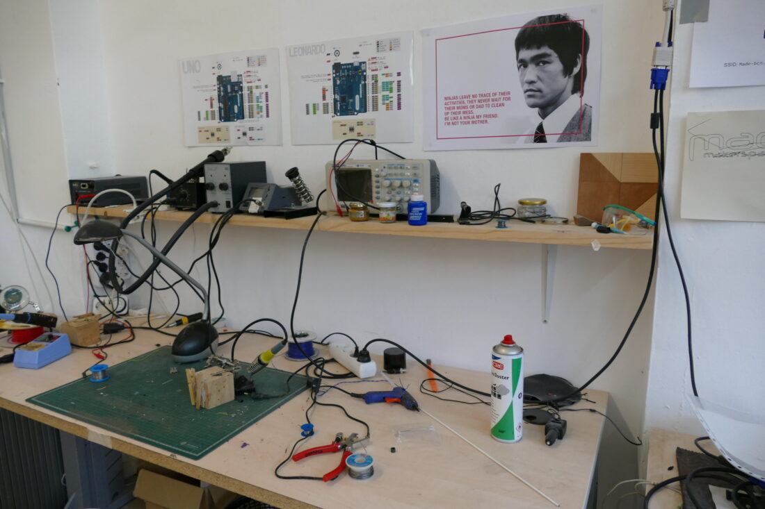 Electronics workbench complete with poster of Bruce Lee telling you to clean up after yourself.