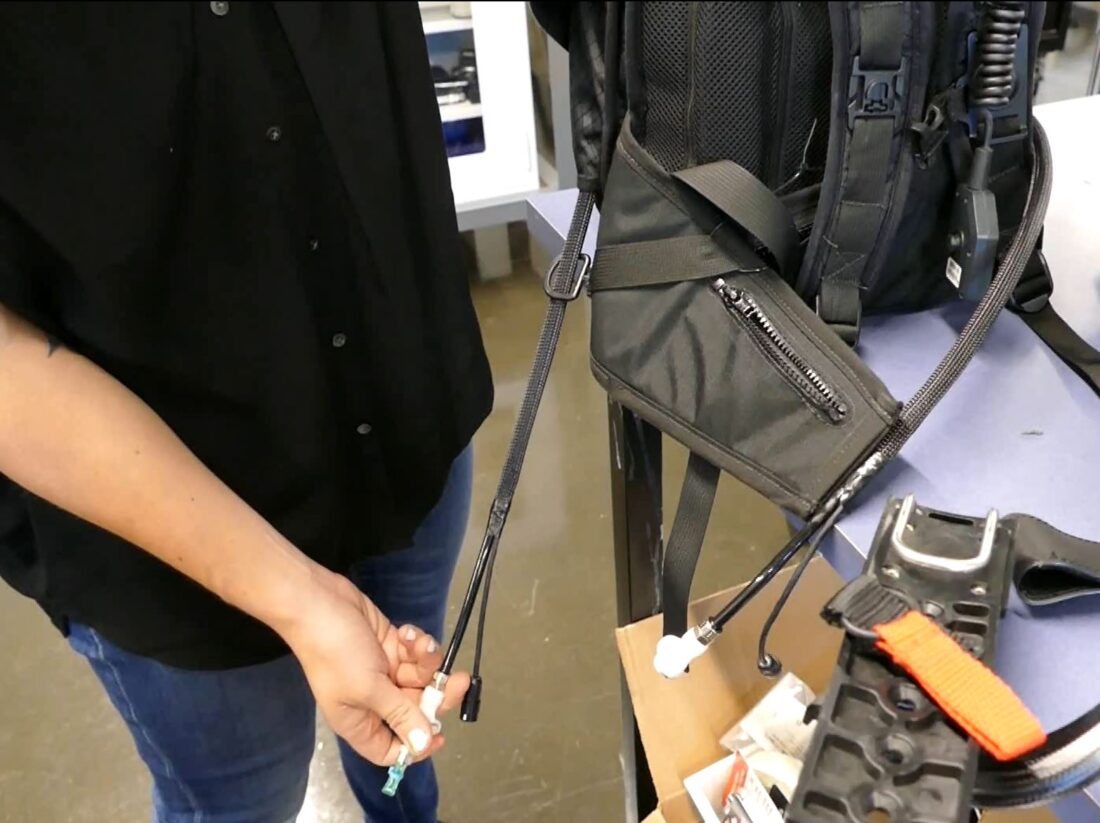 Here, Swartz shows us a retractable cord that plugs into the brace, powering the exoskeleton.