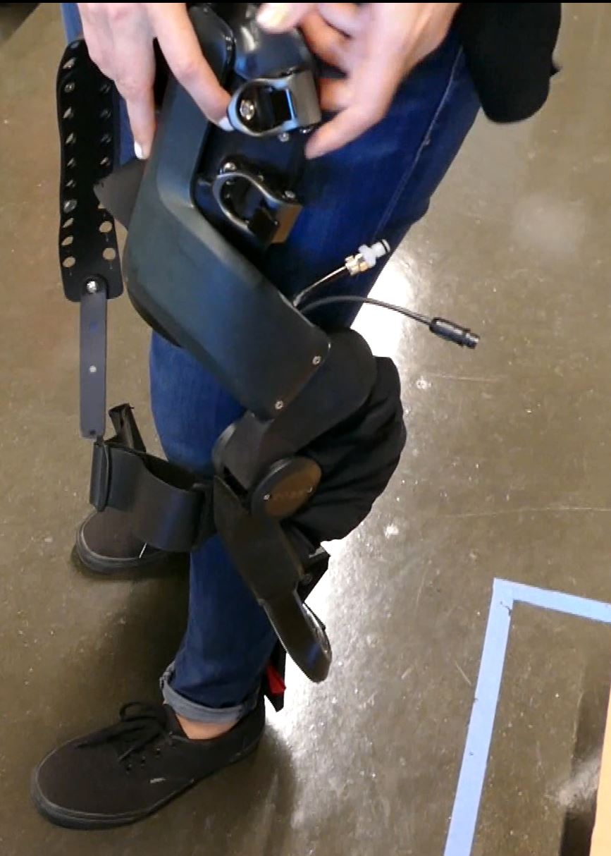 Swartz demonstrates strapping on one of these exoskeleton braces from Roam Robotics.